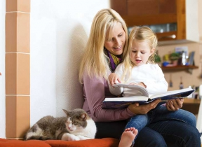 Image: Mum reading a book to child in at home